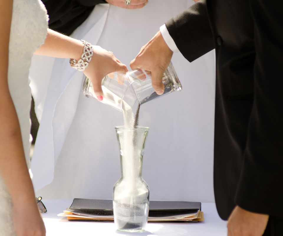 Pouring black and white sand into a unity sand vase