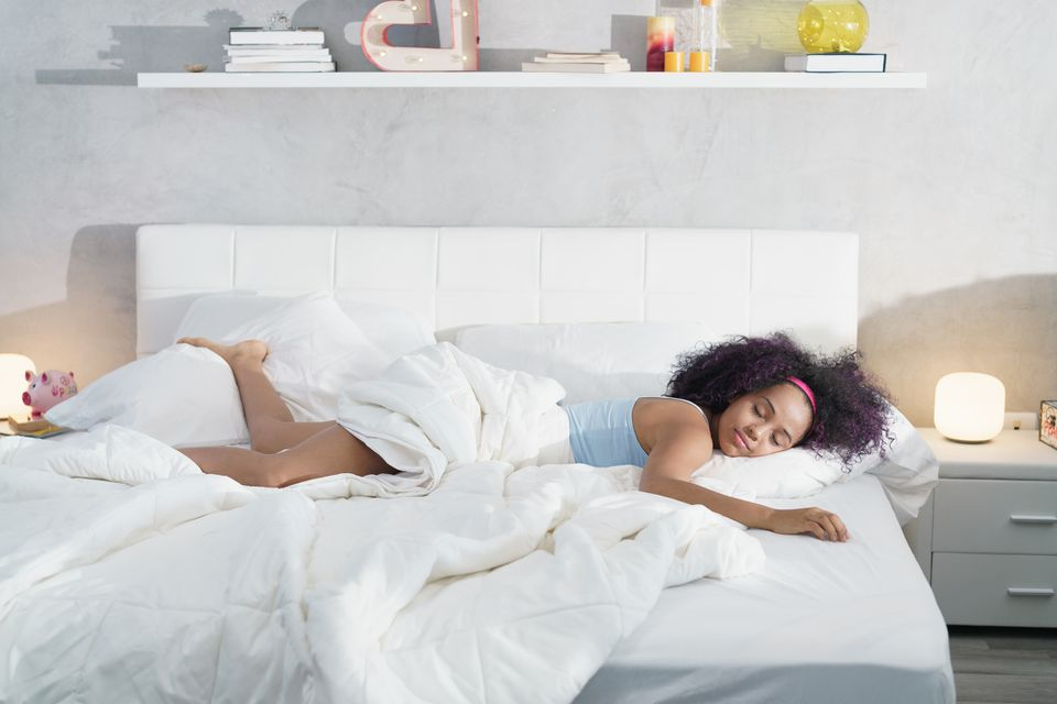 Happy woman sleeping on a large mattress