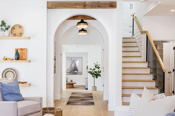 Decorated hallway with white arched walls next to staircase