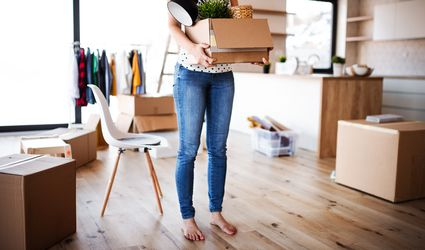 A midsection of young woman carrying a moving box in a new home.