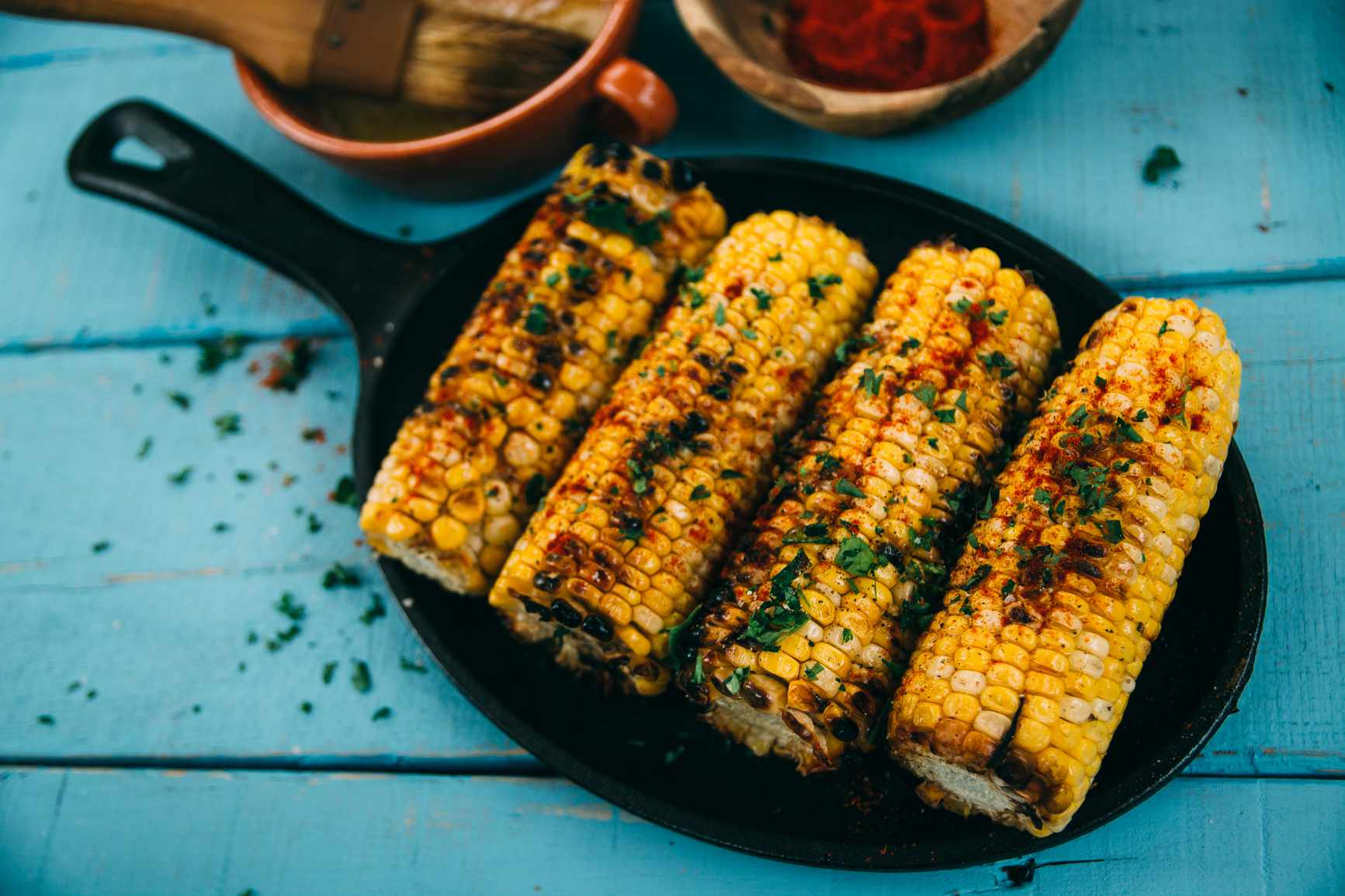 Corn sprinkled with chili in cast iron skillet..