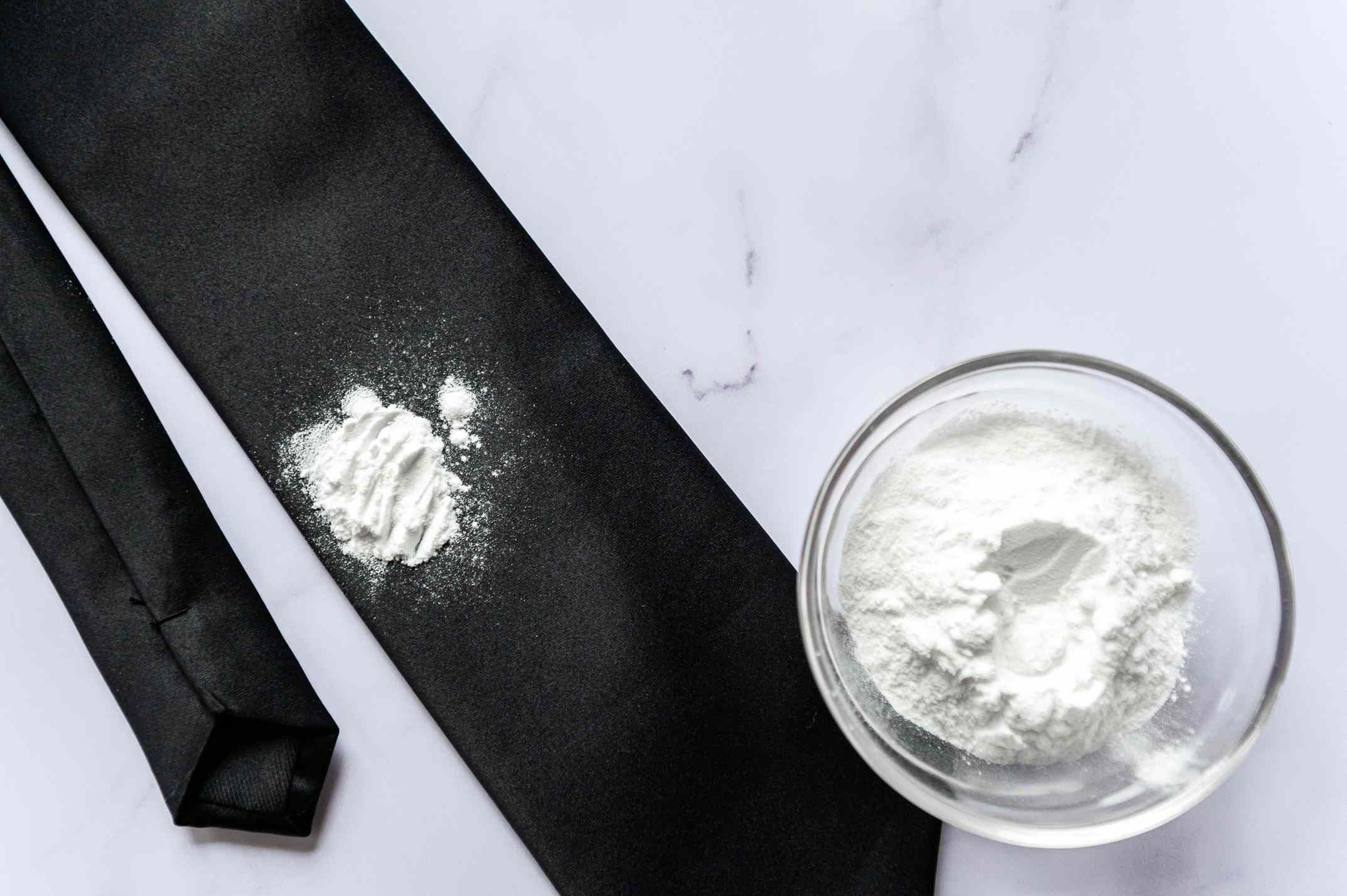 Talcum powder on a black tie and in a small bowl