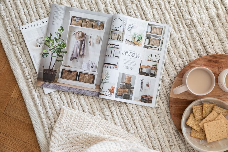 Home decor catalogs laid open on ground next to food tray