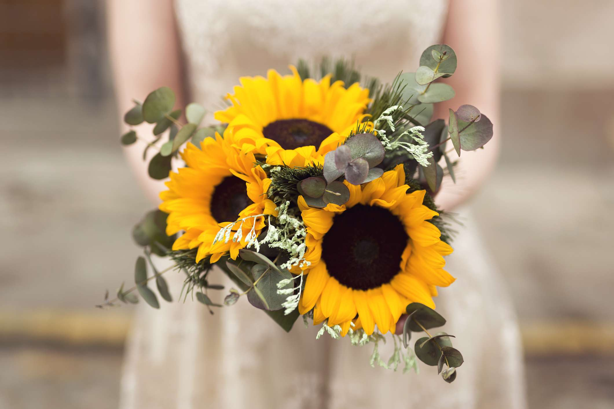 Close up of a bride holding a sunflower wedding