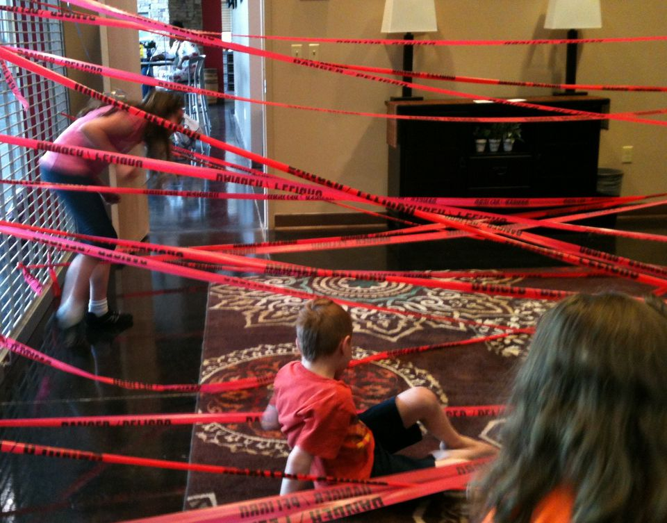 A group of children navigating a red taped room