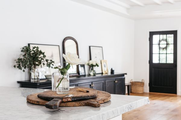 White walled entryway with dark cabinet and framed pictures on top behind marbled counter with white flower in glass vase