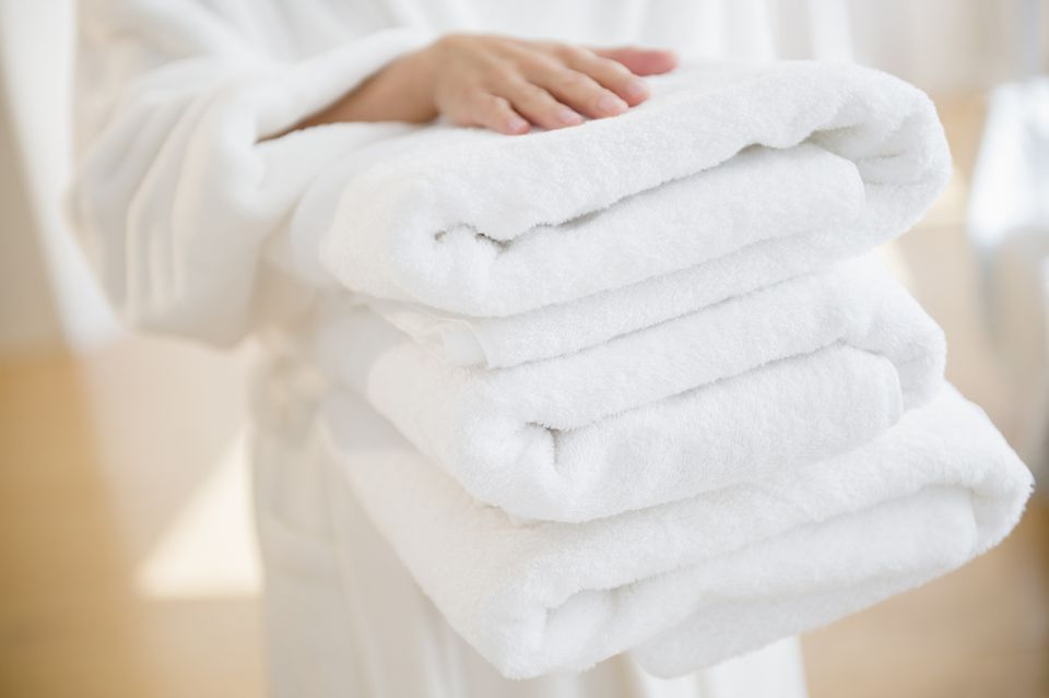 Mixed race woman carrying stack of clean towels