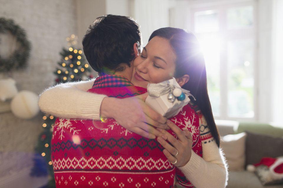 Grateful girlfriend with Christmas gift hugging boyfriend
