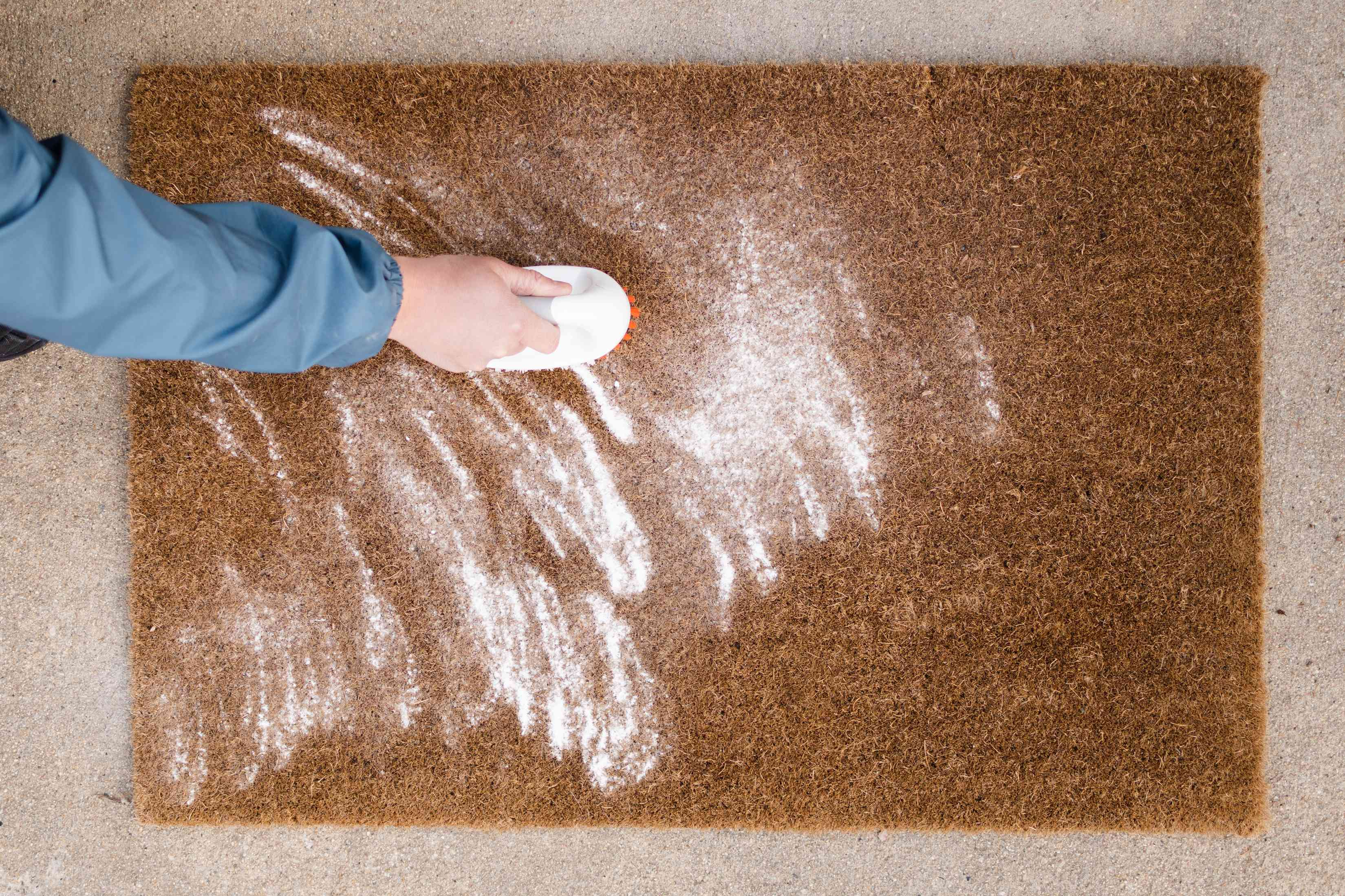 Baking soda sprinkled on brown doormat and brushed through to remove odors