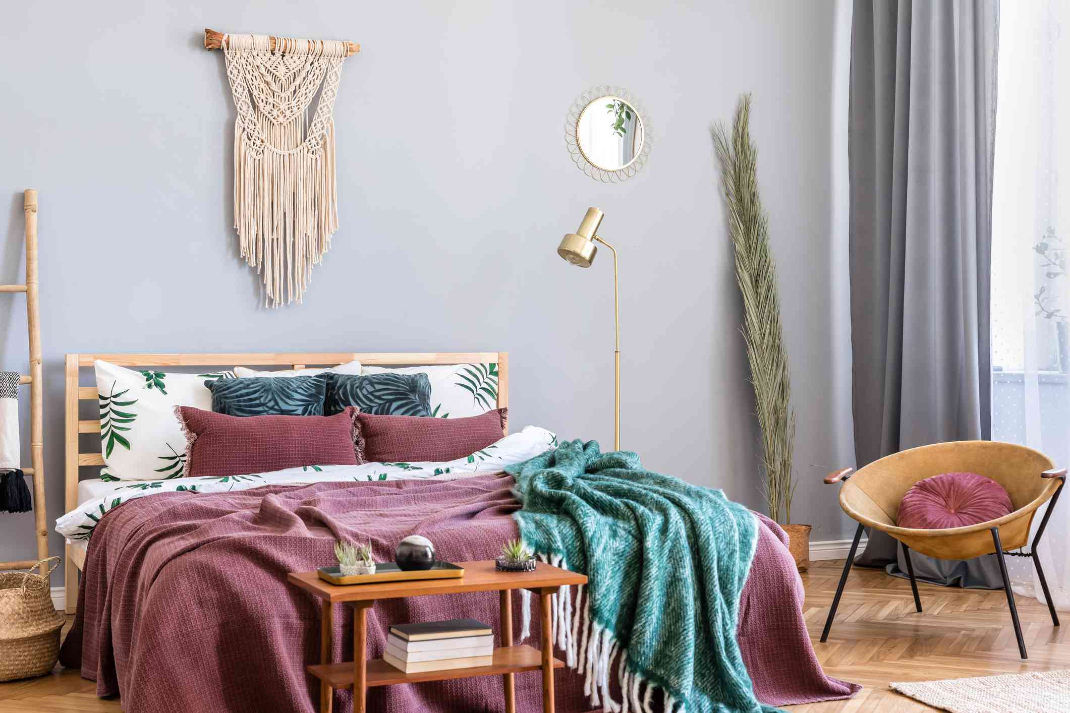 Stylish and luxury interior of bedroom with design furnitures, honey yellow armchair, gray macrame, gold lamp and elegant accessories. Beautiful bed sheets, blankets and pillows