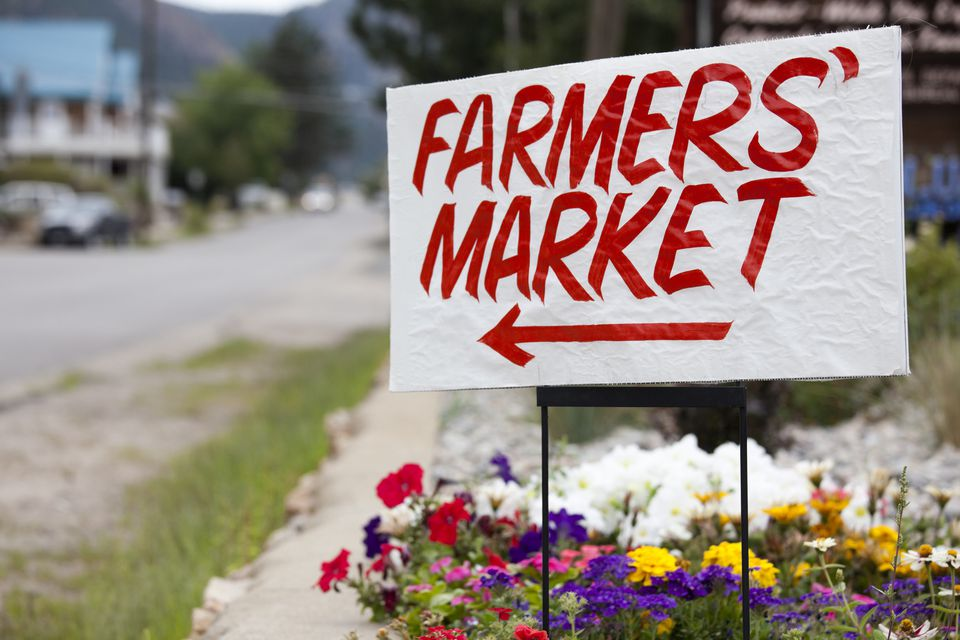 A farmers market sign written in a bold, red, all-caps font