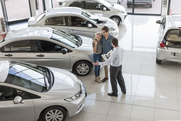 Car dealer showing new car to young couple in showroom