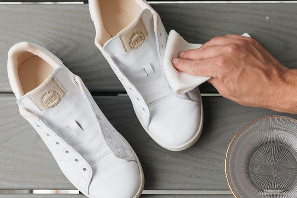 person cleaning white shoes