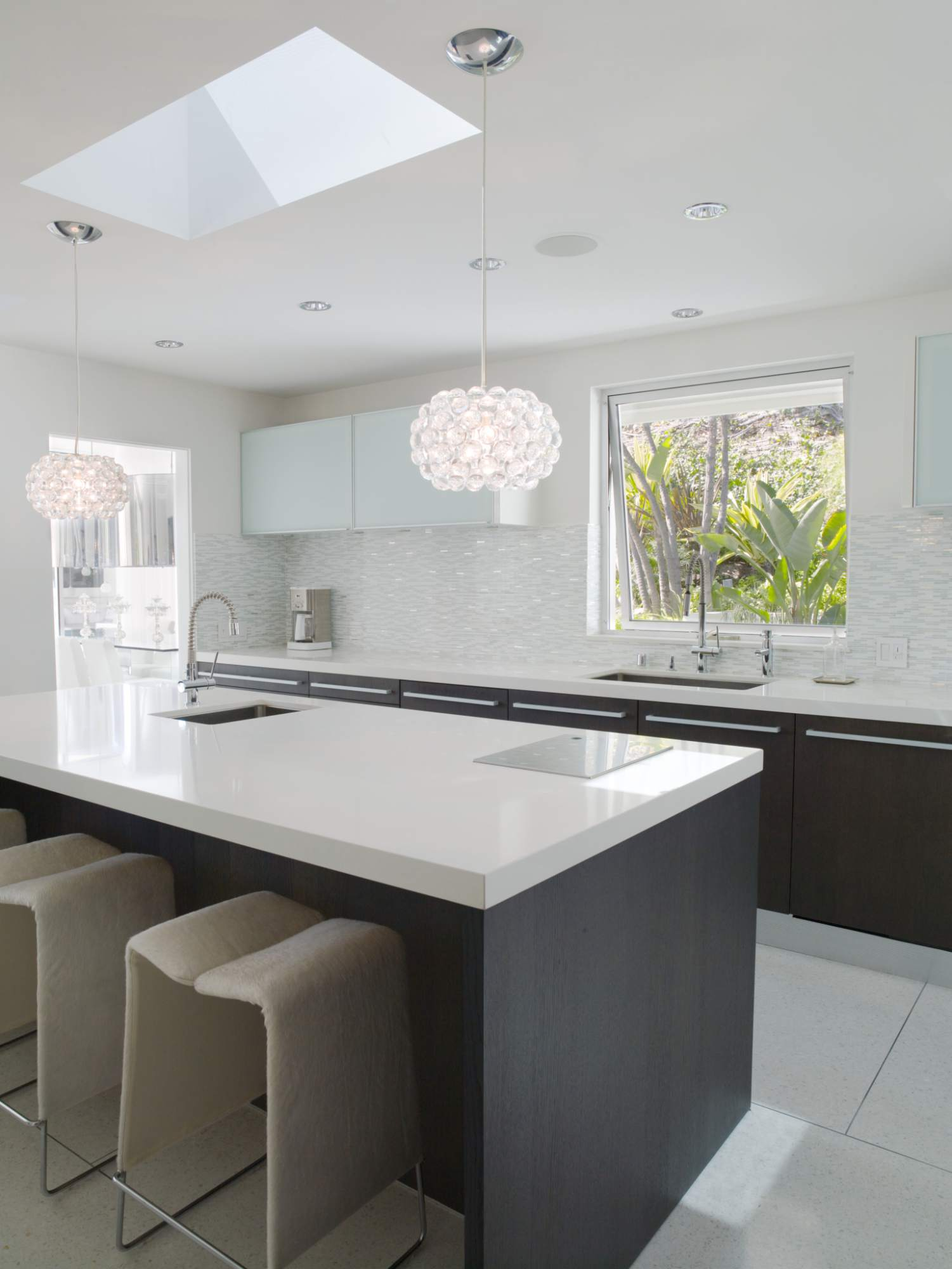 White upper cabinets with white backsplash and white Countertops with dark base cabinets