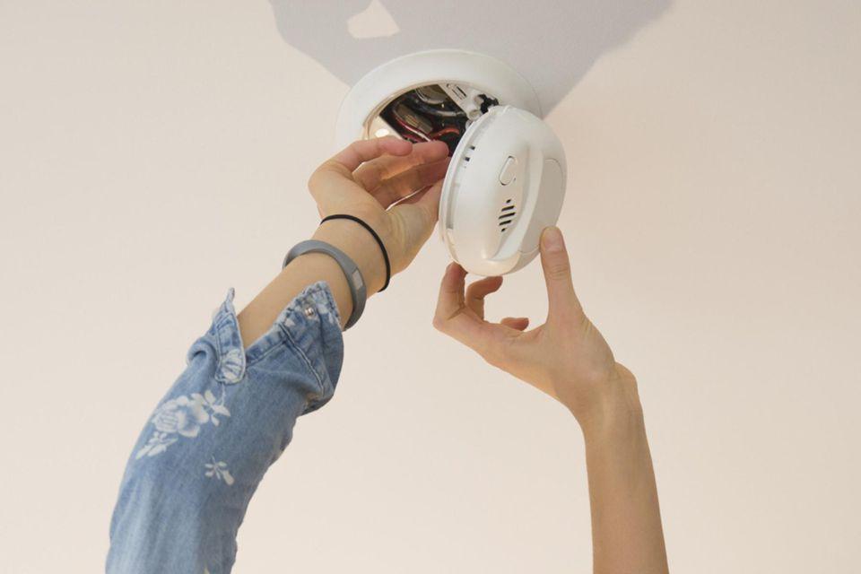 Woman fixing smoke detector