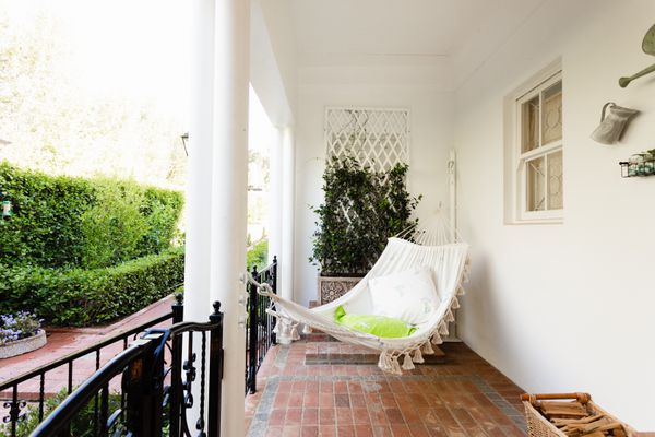 Outdoor porch with brick floor and white hammock hanging between wall and column