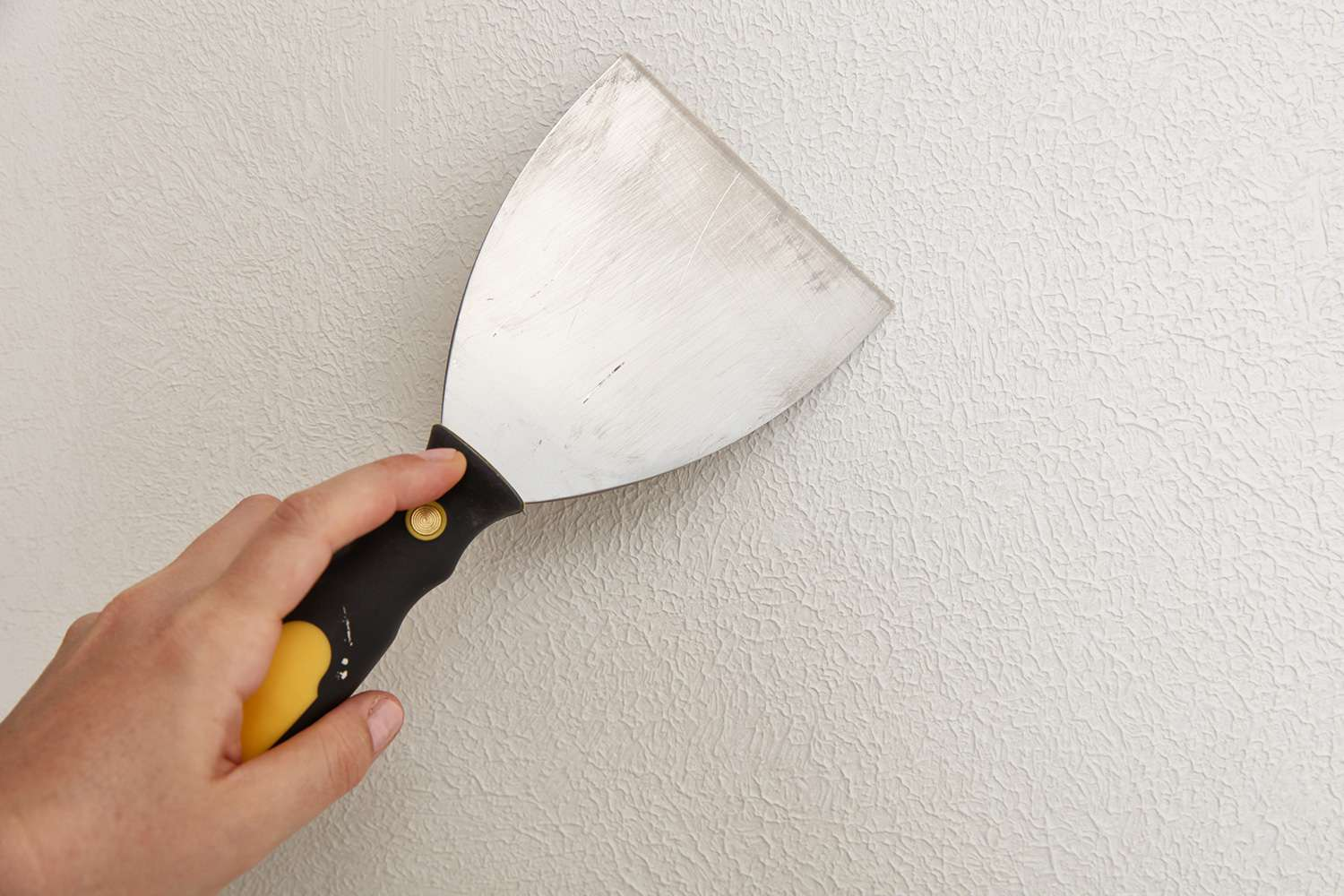 Use drywall knife to smooth out the textured surface