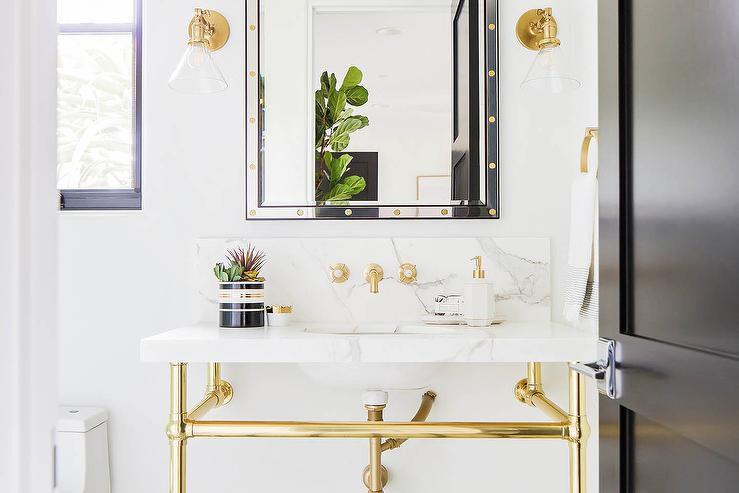placa para salpicaduras y lavabo de mármol blanco en un baño con accesorios de oro