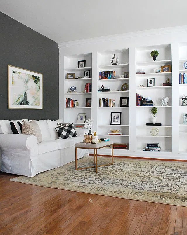 A living room with built in bookshelves