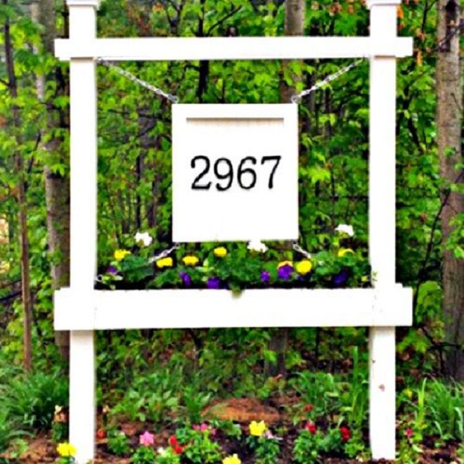 A white address number sign with a flower box.