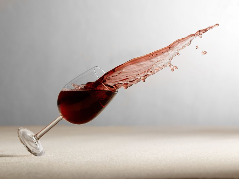 A wine glass frozen in the middle of falling over