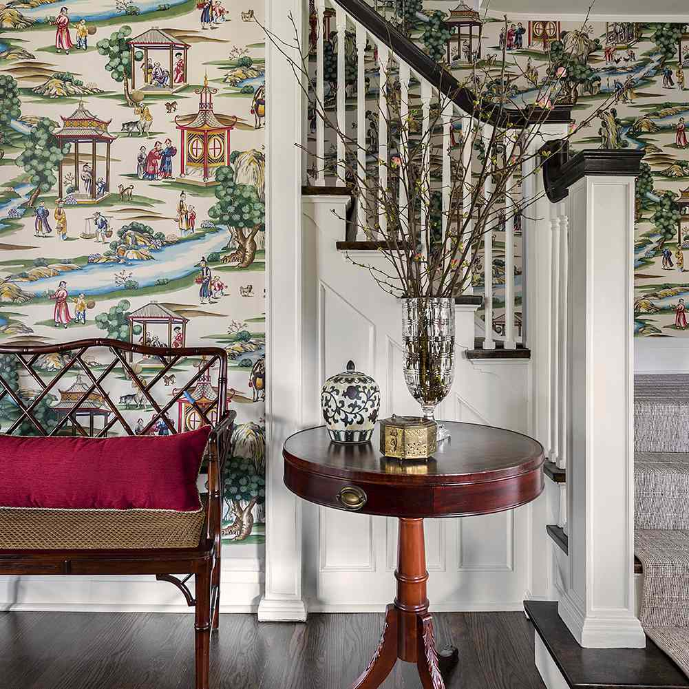 Chinoiserie wallpaper adorns a traditional entryway to a home with a Chinese chippendale bench and an antique wood side table