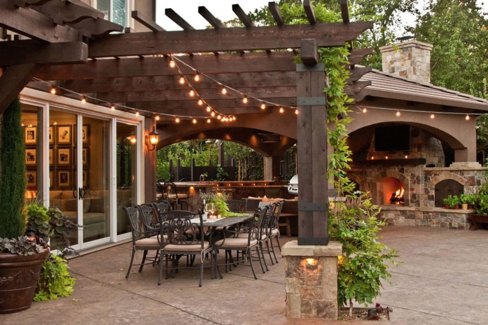 covered patio with outdoor dining room, fireplace and twinkly lights