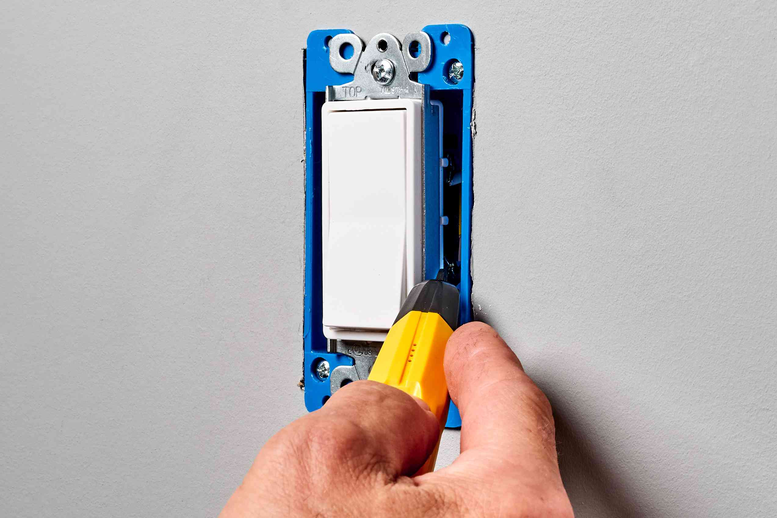 Wall switch's cover plate removed and tested for power with non-contact circuit tester