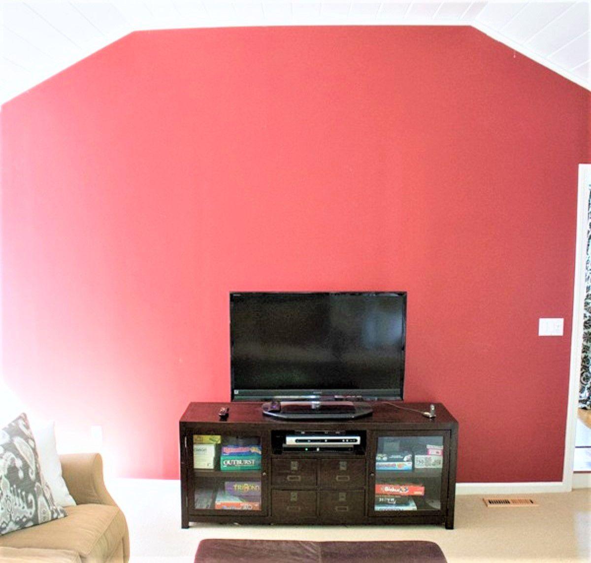 Sala de estar roja con centro de entretenimiento y televisión antes del cambio de imagen