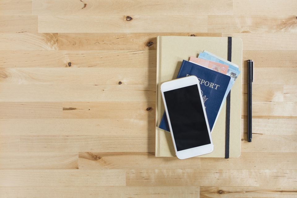 Diario, pasaporte con papel moneda, teléfono inteligente y bolígrafo sobre mesa de madera