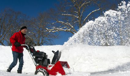 Man using gas snowblower.
