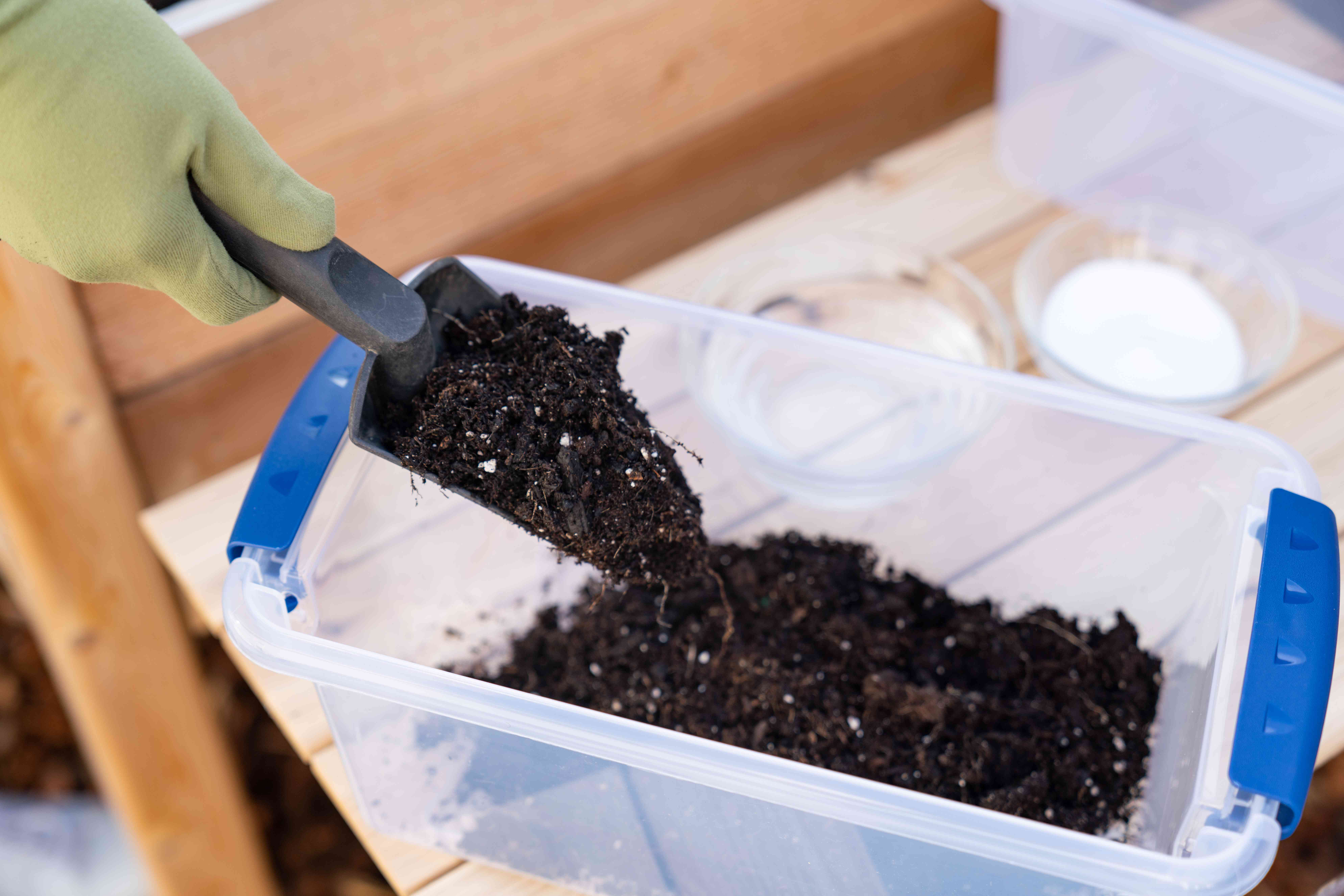 person scooping a soil sample into a container
