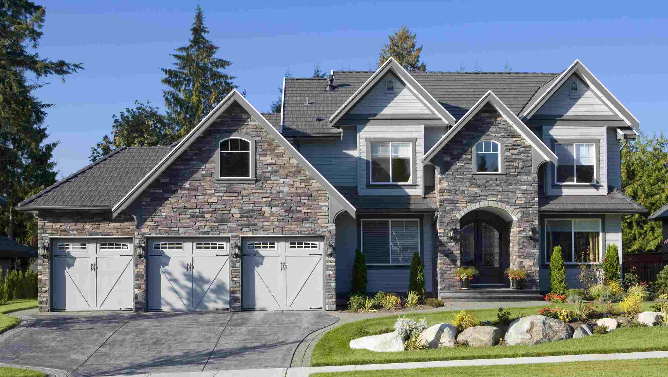 Property with stone garage and house entry, stone driveway, and boulders in an island planting bed.