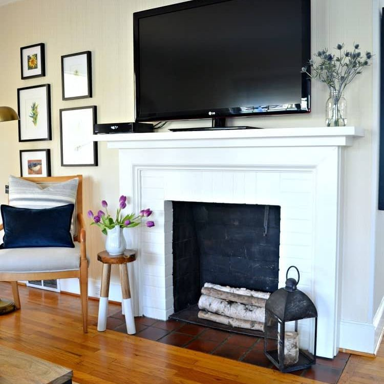 A white fireplace with a TV on top
