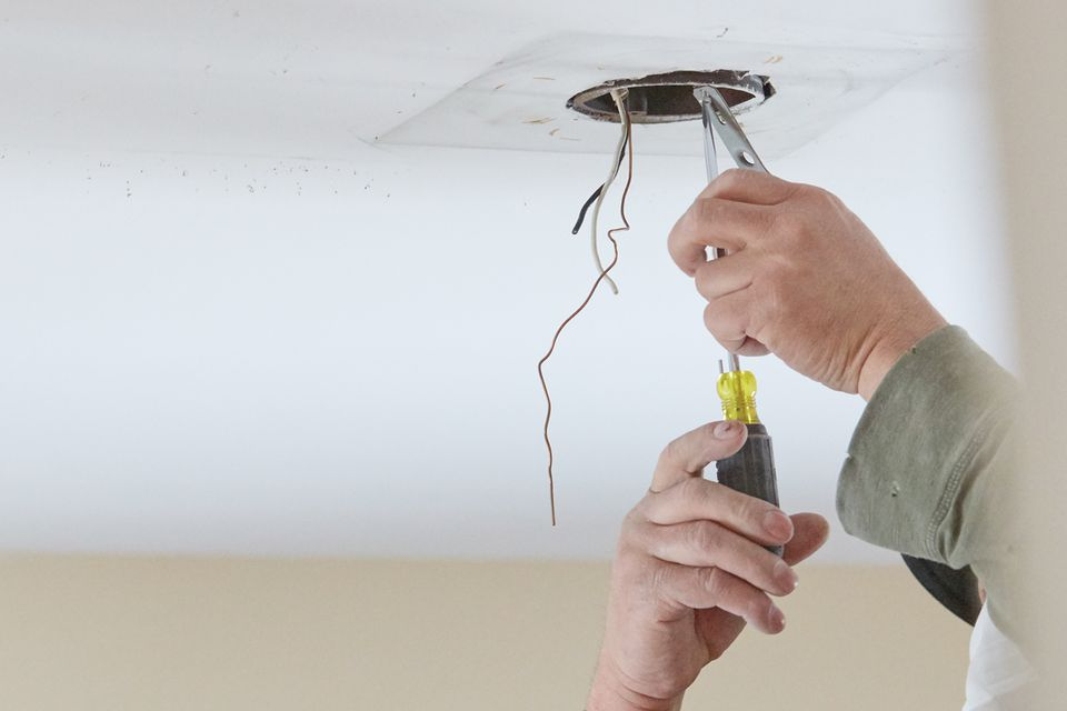 Wires dangling from recessed lighting hole in ceiling while being worked on