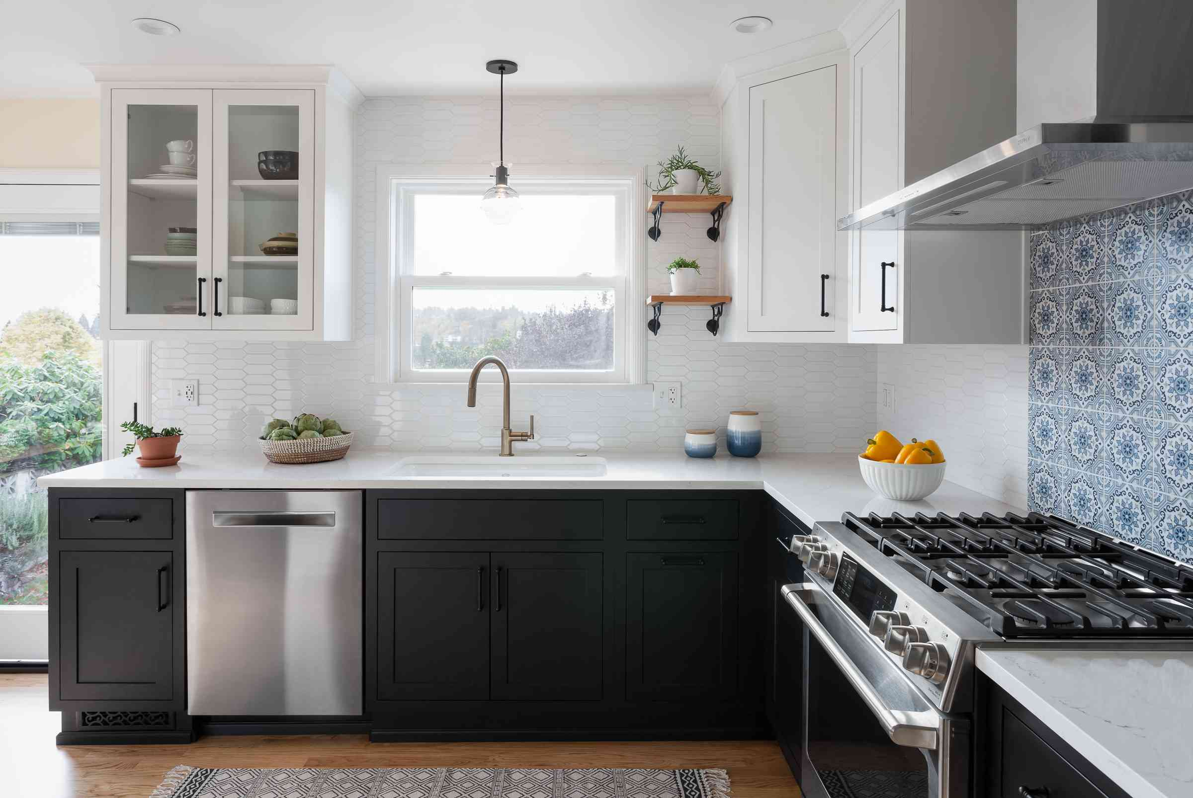 A kitchen with black lower cabinets, white uppers, and a blue stove backsplash