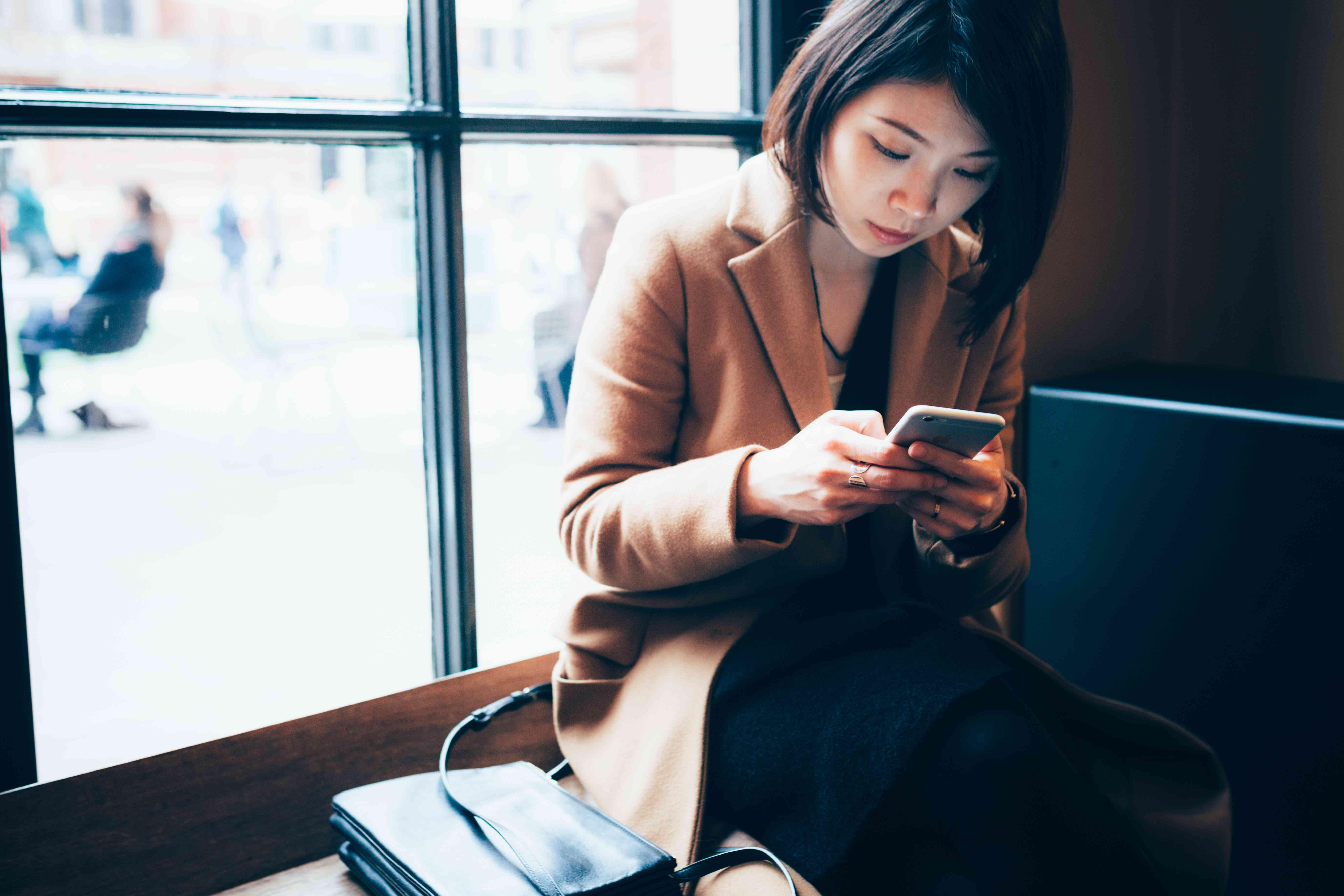 mujer que usa el teléfono celular en la biblioteca