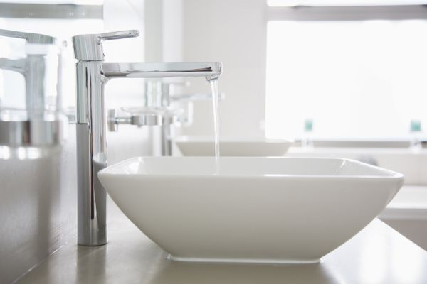 Water pouring from faucet in modern bathroom