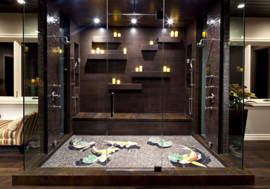 A double shower with dark tile and candles
