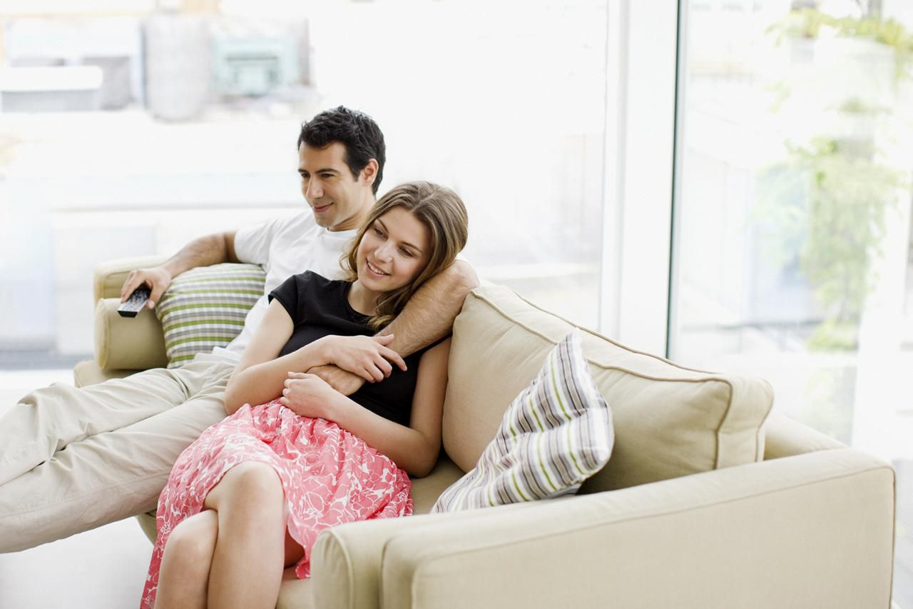 Couple sitting on sofa watching television