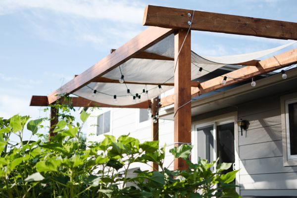 Pergola with wooden beams and string light bulbs hanging underneath with bushes in front