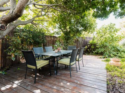 Backyard with lawn table and chairs on wooden patio under tree branches