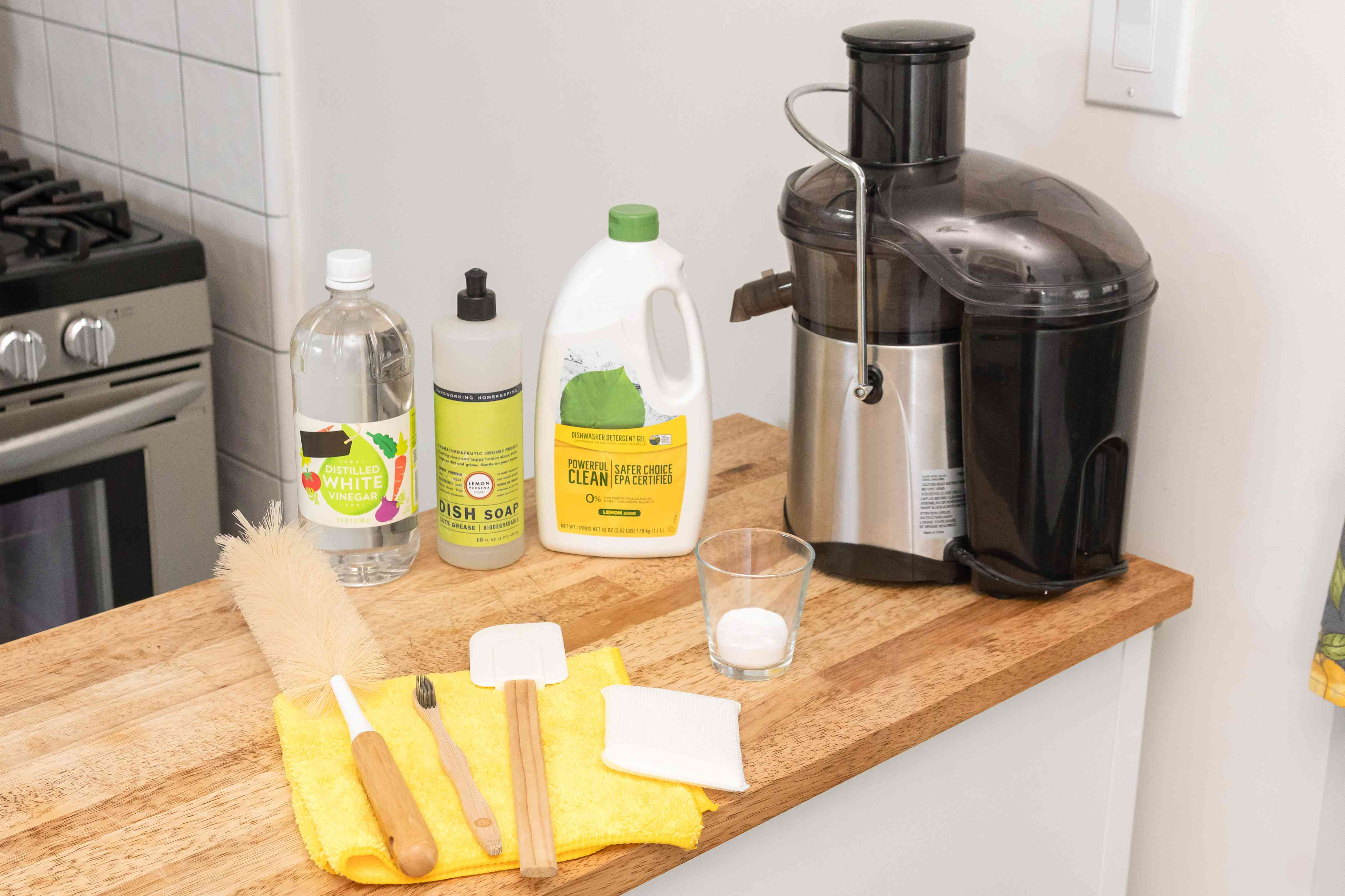 Materials and tools to clean a juicer on wooden surface in kitchen