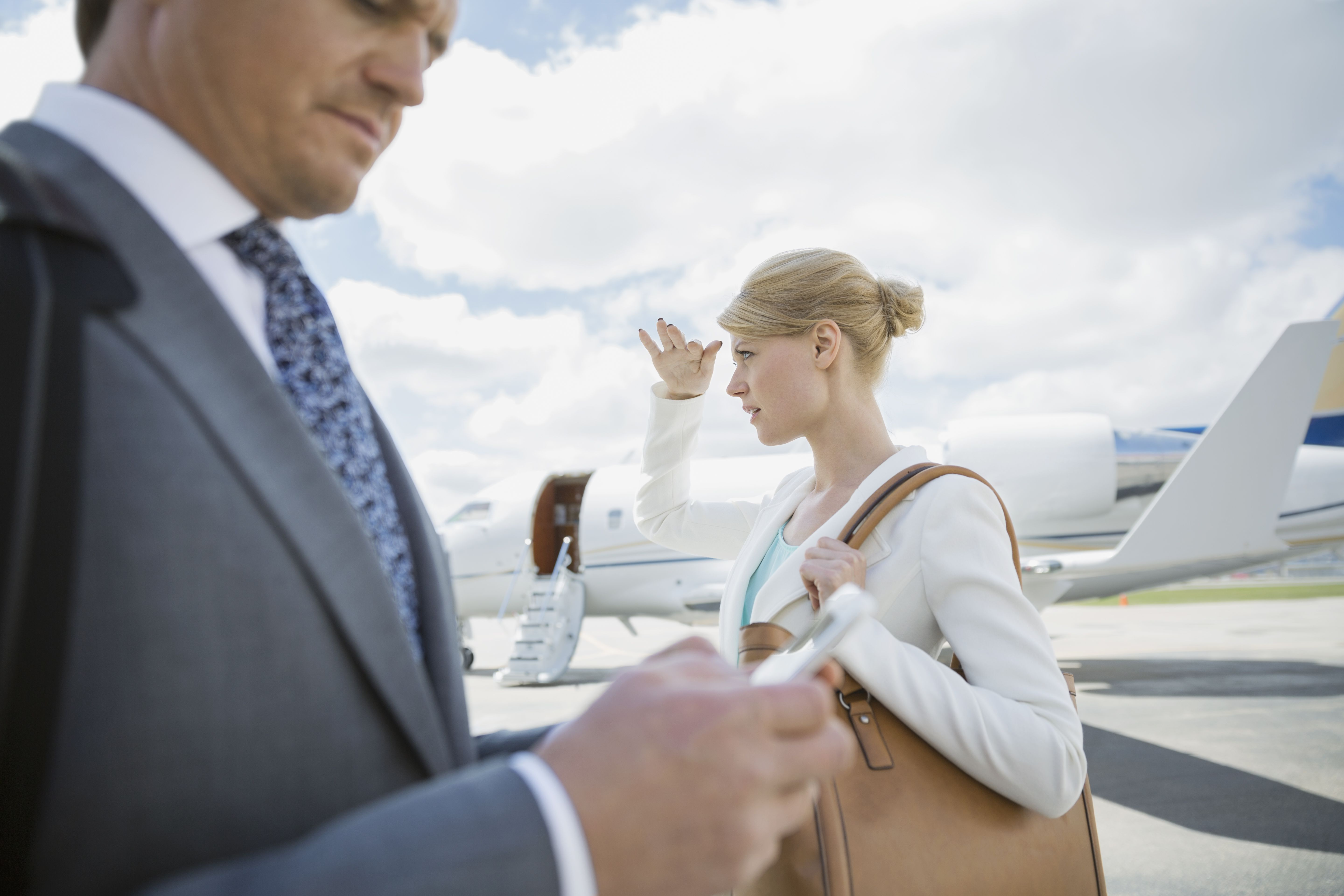 Business people on tarmac with corporate jet