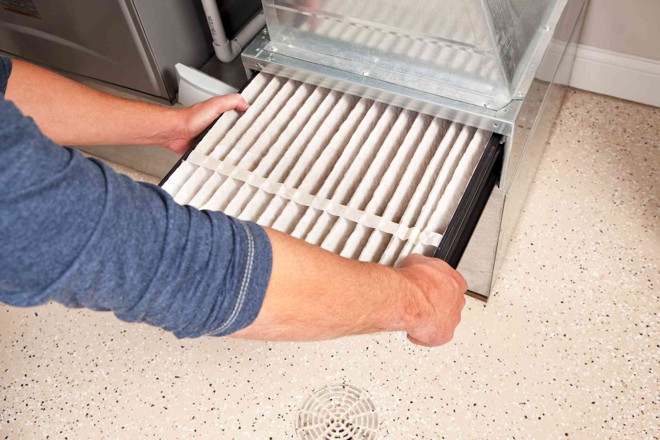 Hands Changing Furnace Air Filter