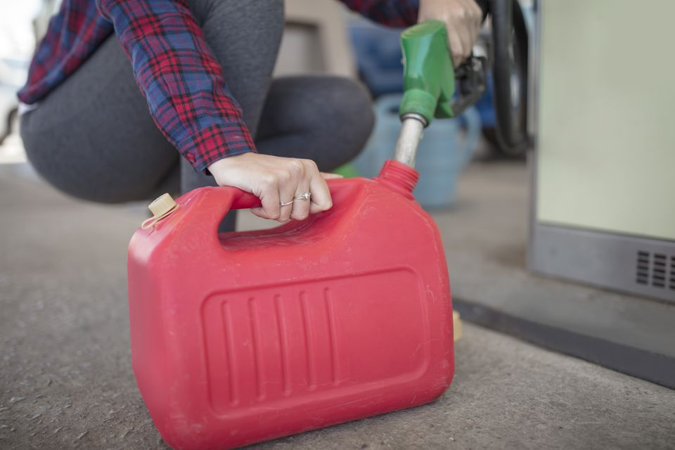 Woman filling up canister at fuel station