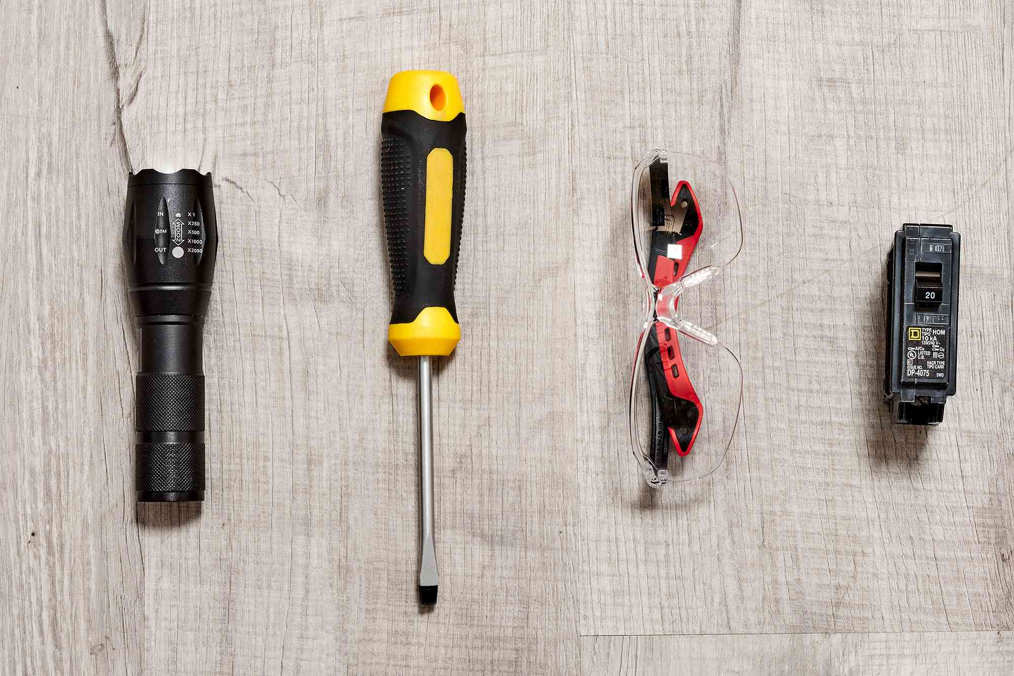 Flashlight, screwdriver, safety glasses and new circuit breaker for replacing