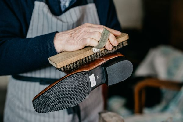 man cleaning leather shoe