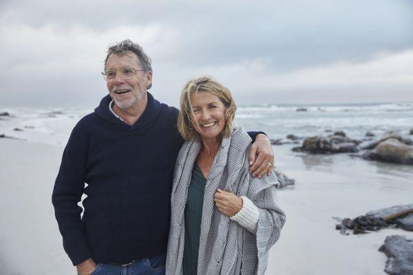 Portrait smiling senior couple hugging on stormy beach