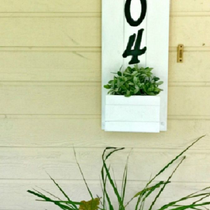 A house number sign with a planter in the bottom.